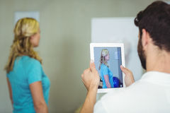 Physiotherapist taking a photograph of a patient with digital table. At clinic Royalty Free Stock Photography