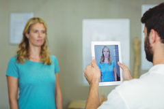 Physiotherapist taking a photograph of a patient with digital table. At clinic Stock Photo