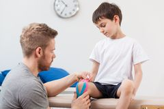 Physiotherapist taping a child royalty free stock image