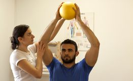 Physiotherapist training with patient. Young female Physiotherapist training with patient. hand exercises with ball Royalty Free Stock Images