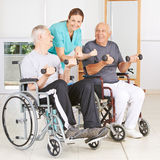 Physiotherapist with two senior men in wheelchairs Stock Photo