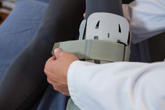 Physiotherapist tying leg pad Stock Photo