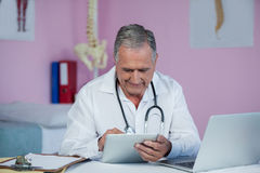 Physiotherapist using digital tablet. In clinic Royalty Free Stock Photos