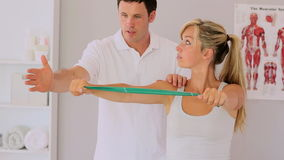 Physiotherapist using a resitance band with his patient Royalty Free Stock Photo