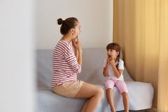 Physiotherapist wearing striped casual shirt working on speech defects or difficulties with small child girl at home while sitting