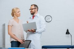 physiotherapist in white coat with laptop and female patient looking at each other