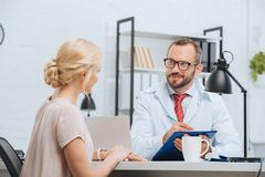 physiotherapist in white coat making notes in notepad with female patient near by during appointment