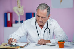 Physiotherapist writing on clipboard Royalty Free Stock Photography