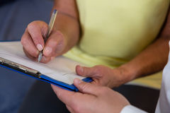 Physiotherapist writing on clipboard in clinic Stock Image