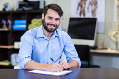 Physiotherapist writing on a clipboard Royalty Free Stock Photo