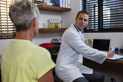 Physiotherapist writing prescription on clipboard for senior patient Stock Image
