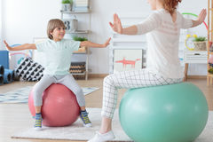 Young boy doing stretching exercise. Physiotherapist and young boy doing stretching exercise on colorful balls in bright room Stock Images
