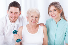 Physiotherapists and exercising elderly woman. Portrait of physiotherapists and exercising elderly woman stock photography