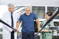 Physiotherapists Motivating Senior Man To Walk Between Parallel. Male and female physiotherapists motivating senior men to walk between parallel bars in fitness royalty free stock photo
