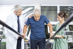 Physiotherapists Motivating Senior Patient To Walk Between Paral. Male and female physiotherapists motivating senior patient to walk between parallel bars in Royalty Free Stock Photography