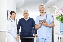 Physiotherapists And Senior Patient In Rehab Center. Portrait of physiotherapists and senior male patient standing in rehab center Stock Photos