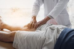 Physiotherapists are using the hands to grip the patient thigh to check for pain and massage in the clinic.  royalty free stock images