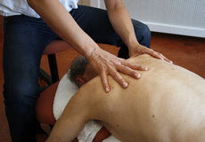 Physiotherapy. Phystiotherapist massaging back of senior male Stock Image