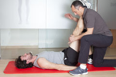 Physiotherapy. Physical therapist with patient in a gym Stock Photos