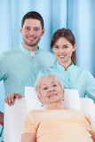Physiotherapy in geriatrics. Closeup of two young physiotherapist and geriatric patient Royalty Free Stock Photos
