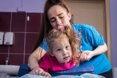 Physiotherapy in medicine clinic with a baby having a cerebral palsy. Mid shot royalty free stock photography