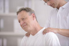 Physiotherapy: Physiotherapist massaging patient Stock Images