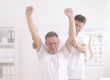 Physiotherapy: Senior man and physiotherapist royalty free stock photos
