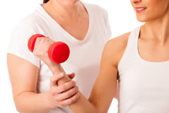 Physiotherapy - therapist doing arm  excercises with dumbbells f. Or improving arm strenght and coordination  with a patient to recover  after injury Royalty Free Stock Image