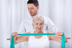 Physiotheraqpist assisting elderly woman in exercising Royalty Free Stock Photos