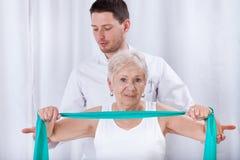 Physiotheraqpist que ayuda a la mujer mayor en el ejercicio Imagen de archivo libre de regalías