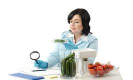 Phytosanitary technician stares at the cucumber Royalty Free Stock Image