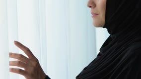 Piękna arabska kobieta czekać na męża w hijab, patrzeje w okno, w górę zbiory