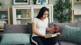 Piękna Azjatycka dziewczyna jest czytelniczym książką, pić herbacianego obsiadanie na kanapie w domu i cieszyć się czas wolnego i zbiory