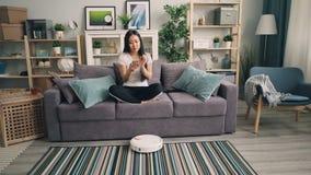 Piękna Azjatycka dziewczyna obraca dalej mechaniczny próżniowy czysty wtedy siedzieć na kanapie, używać smartphone cieszy się dog zbiory