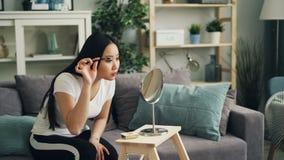 Piękna Azjatycka dziewczyna patrzeje lustrzanego obsiadanie na kanapie w domu stawia dalej uzupełnia używać tusz do rzęs i twarz  zbiory