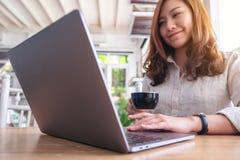 Piękna azjatykcia kobieta używa i dotykający na laptopu touchpad podczas gdy pijący kawę obraz stock