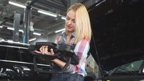 Piękna blond dziewczyna koncentrował na pracować z cyfrową pastylką zbiory wideo