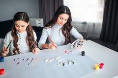 Piękna brunetki caucasian matka i córka malujemy wpólnie w pokoju Siedzą przy stołem i rysują Spokój cocentrated obrazy stock