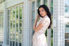 Piękna brunetki dziewczyna pozuje w beżowej colour sukni na zewnątrz kawiarni blisko drewnianej i szklanej ściany zdjęcie royalty free