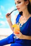Piękna brunetki kobieta jest ubranym błękitnego bikini, cieszy się basenu, lato czas fotografia stock