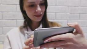 Piękna brunetki kobieta ogląda serial w hełmofonach na telefonie komórkowym na ceglanym biel ściany tle zbiory