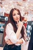 Piękna długie włosy azjatykcia uśmiechnięta dziewczyny młoda kobieta w sklepowym supermarkecie kosmetyki, pachnidła, bezcłowi zdjęcia royalty free