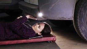 Piękna dziewczyna, brunetka, kłama pod samochodem i dociska śruby zbiory