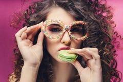 Piękna dziewczyna je zielonego macaroon w ciasteczek opatrunkowych szkłach obraz stock