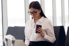 Piękna dziewczyna przy lotniskiem międzynarodowym, pije kawę iść podczas gdy czekać na jej lot Żeński pasażer przy fotografia stock