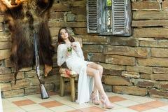 Piękna dziewczyna w białej sukni pije mojito obsiadanie obok łowieckiego karabinu zdjęcie stock