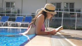 Piękna dziewczyna w kapeluszu i okulary przeciwsłoneczni czytelniczej książce przy basenem Młoda kobieta relaksuje przy ciepłym s zbiory