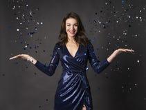 Piękna elegancka brunetki kobieta, ono uśmiecha się, ubierająca w genialnej błękit sukni rzuca świąteczną błyskotliwość i confett zdjęcie royalty free