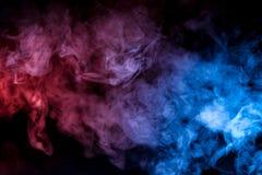 Piękna horyzontalna kolumna dym w neonowym jaskrawym świetle błękit pomarańcze na czarnym tle i menchie exhaled z fotografia stock