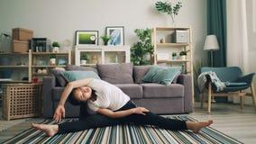 Piękna młoda dama robi fizycznym ćwiczeniom rozciąga nogi i ciała obsiadanie na podłodze elegancki nowożytny w domu zbiory wideo